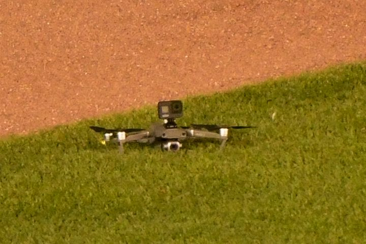 A drone lies on the grass after it landed in center field, before taking off again and flying out of the stadium, during the