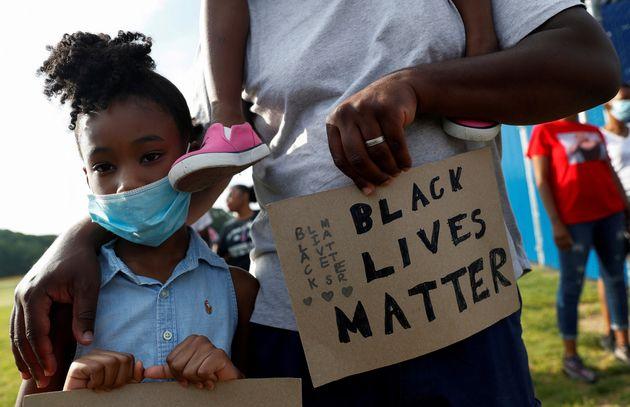 ジョージ・フロイドさんの死に抗議するBLMの集会で、父親と参加する黒人の少女=2020年6月10日、米国ニューヨーク州