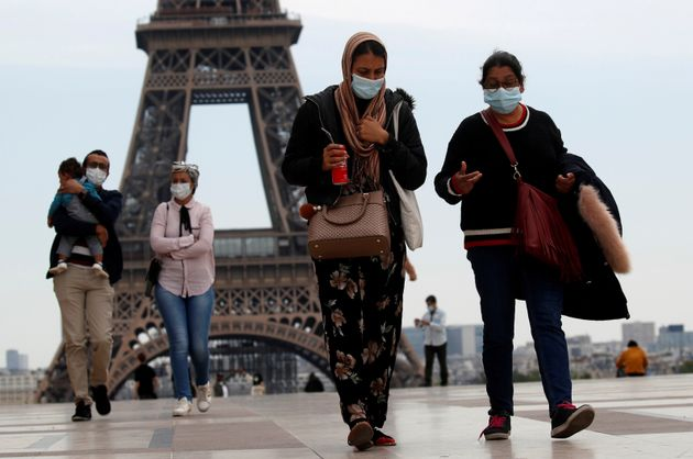 People wearing face masks walk at Trocadero square near the Eiffel Tower, as France began a gradual end...