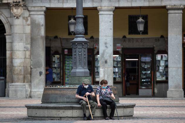 스페인 마드리드 시내에서 마스크를 쓴 한 노부부가 휴식을 취하고 있다. 마드리드는 코로나19 확산이 다시 이어지는 지역에 대해 선별적인 봉쇄조치를 단행하기로 했다. 2020년