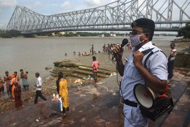 A police officials issues warnings for devotees performing rituals on the bank of river Hooghly to mark...