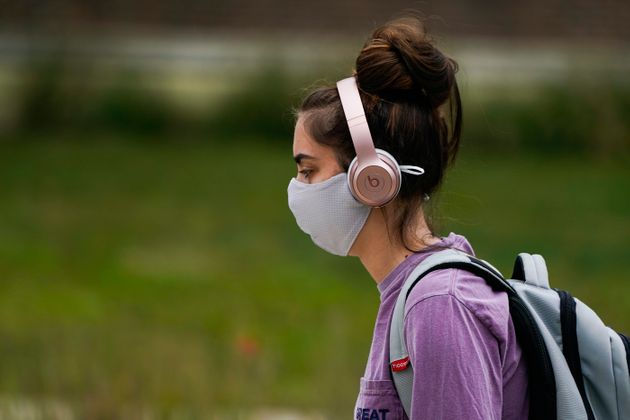 A masked student walks through the campus of Ball State University in Muncie, Ind., Thursday, Sept. 10,