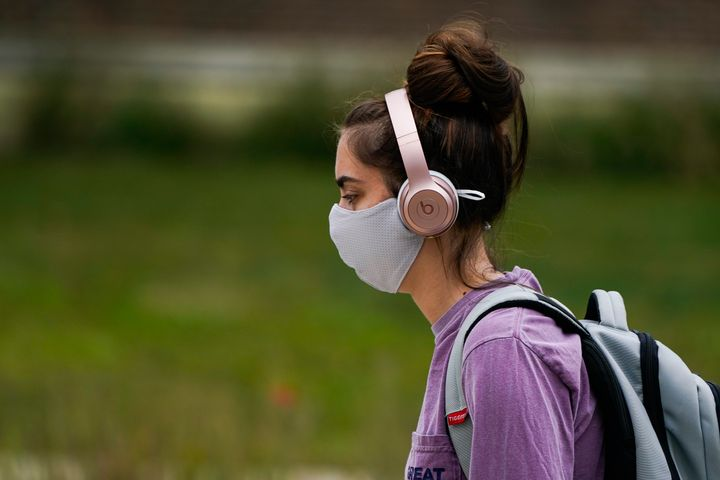 A masked student walks through the campus of Ball State University in Muncie, Ind., Thursday, Sept. 10, 2020.