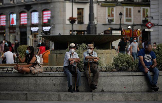 Dos hombres con mascarilla sentados en una fuente de Madrid el 16 de septiembre de 2020 (Burak Akbulut/Anadolu...