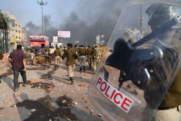 Police walk along a road following clashes at Bhajanpura area of New Delhi on February 24,