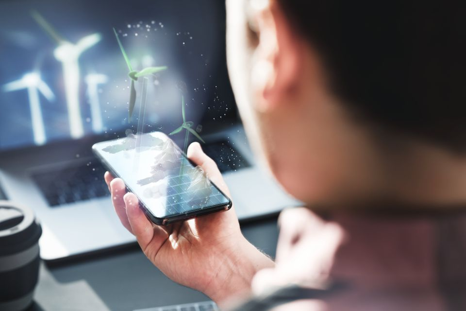 An engineer is working with a futuristic hologram to create alternative energy solutions with wind turbines.