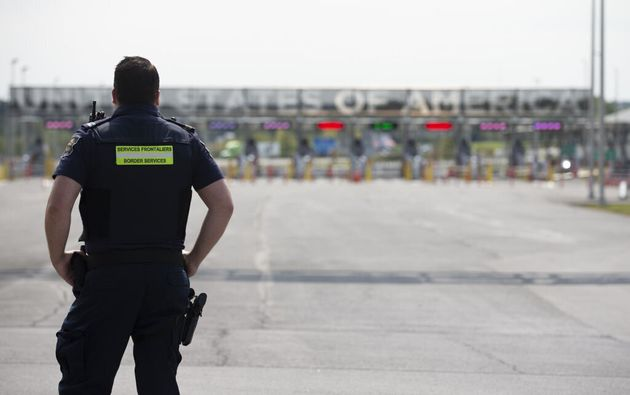 A Canadian border agent stands in front of the U.S.-Canada border in Saint-Bernard-de-Lacolle, Que.,...
