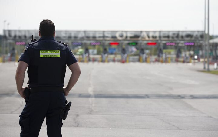 A Canadian border agent stands in front of the U.S.-Canada border in Saint-Bernard-de-Lacolle, Que., on Sept. 16.