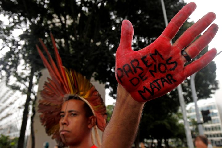 "A man from the Xakriabá people shows his hand covered with the Portuguese phrase: ""Stop killing us"" during a protest a"