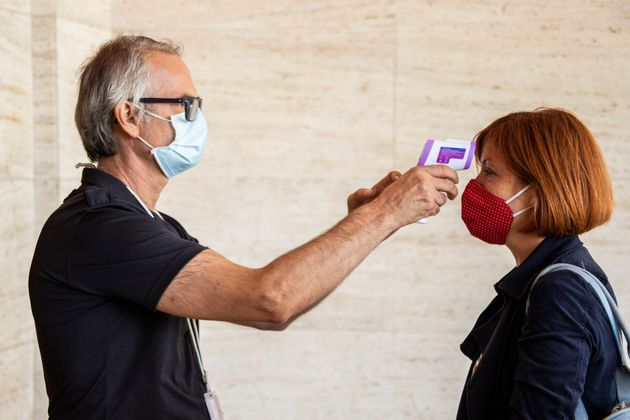 A festival attendee has their temperature checked ahead of the start of the 77th edition of the Venice...