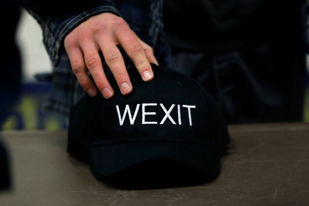 A supporter holds his Wexit hat while attending a rally in Calgary on Nov. 16,