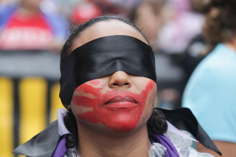 Mulher utiliza venda e tem o rosto pintado de vermelho em protesto no Dia Internacional da Mulher, realizado...