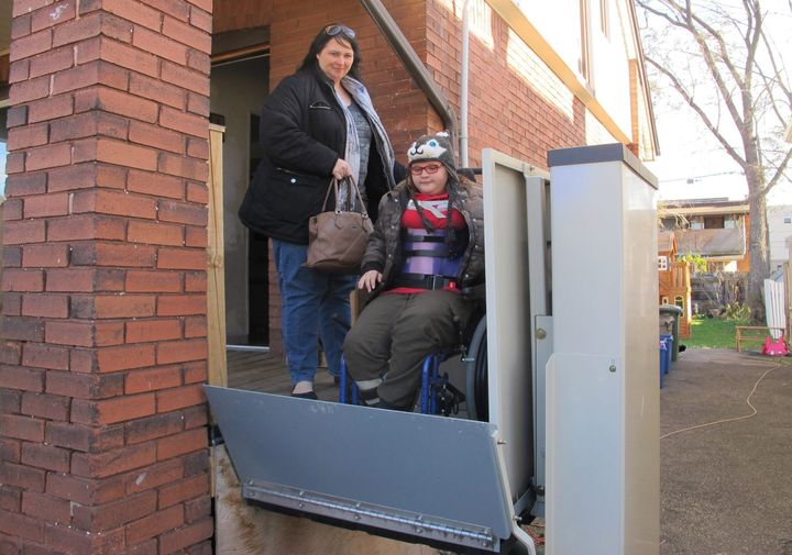 "In this Nov. 21, 2017 photo, Jodi Dean helps her wheelchair-bound daughter Madison, who suffers epilepsy and severe osteoporosis, on an elevator as they leave home for a doctor's visit in Hamilton, Ont. The mother of three received her first basic income check last month and said the extra money gave her family ""the breathing room to not have to stress to put food on the table."""