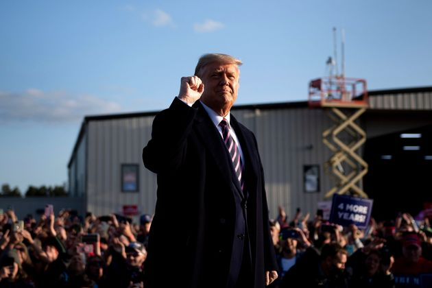 President Donald Trump pumps his fist as he arrives for a