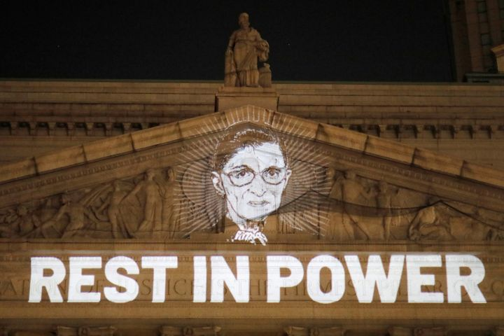 An image of Justice Ruth Bader Ginsburg is projected onto the front of the New York State Civil Supreme Court building in Man