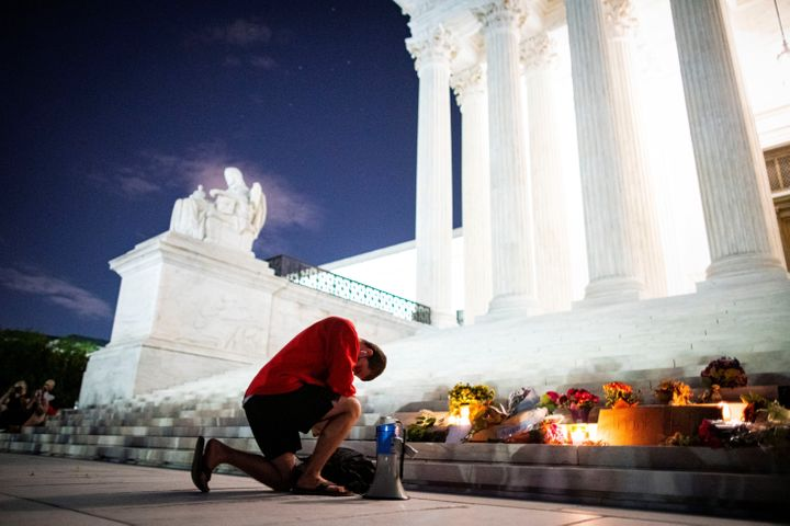 A man kneels outside the Supreme Court before tributes to the Justice Ruth Bader Ginsburg following her death on Friday.