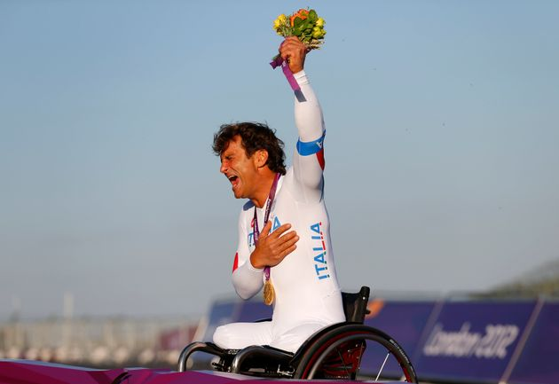 Former F1 and Cart racing car driver Alessandro Zanardi of Italy, celebrates after receiving his gold...