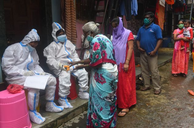 BMC Health worker and Doctor conduct thermal screening and pulse test of a resident at Dharavi during...