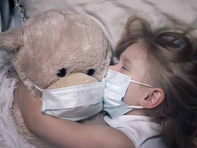 Little girl and big plush bear sleep in medical masks. The concept of childhood diseases, empathy, support...