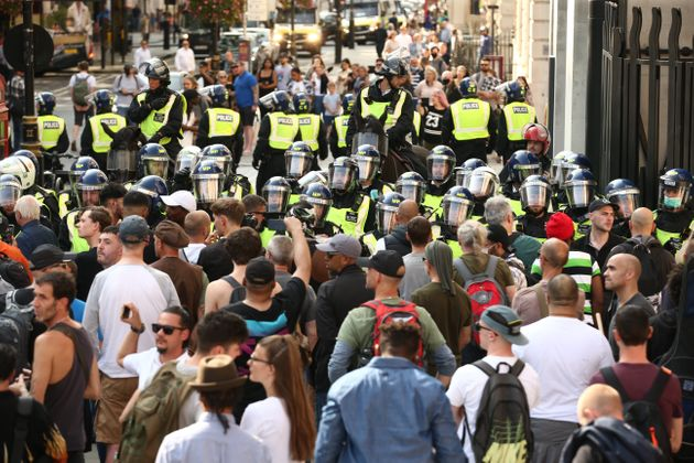 Police presence among demonstrators during an anti-vax protest in London's Trafalgar Square.