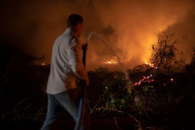 Voluntário utiliza água para debelar chamas que ameaçam ponte no