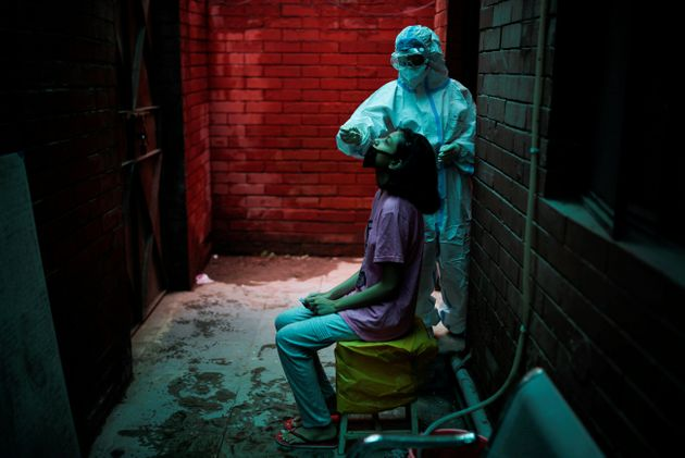 A health worker collects a sample to test for Covid-19 at a local health centre in New Delhi, India August...