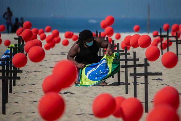 Um manifestante da ONG 'Rio De Paz' amarra uma bandeira brasileira a uma cruz na praia de