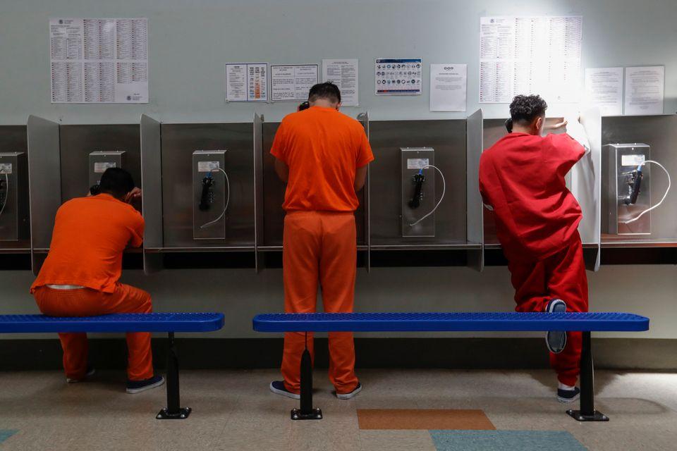 Des détenus parlent au téléphone dans un centre de traitement d'ICE à Adelanto,...