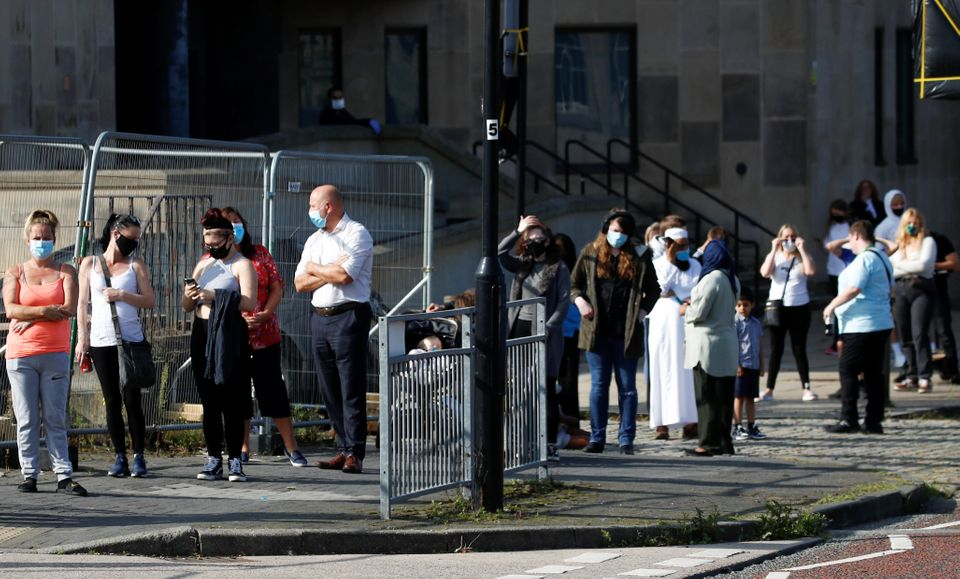 People queue outside a test center to take a coronavirus test in Bolton, in the northwest of England,...