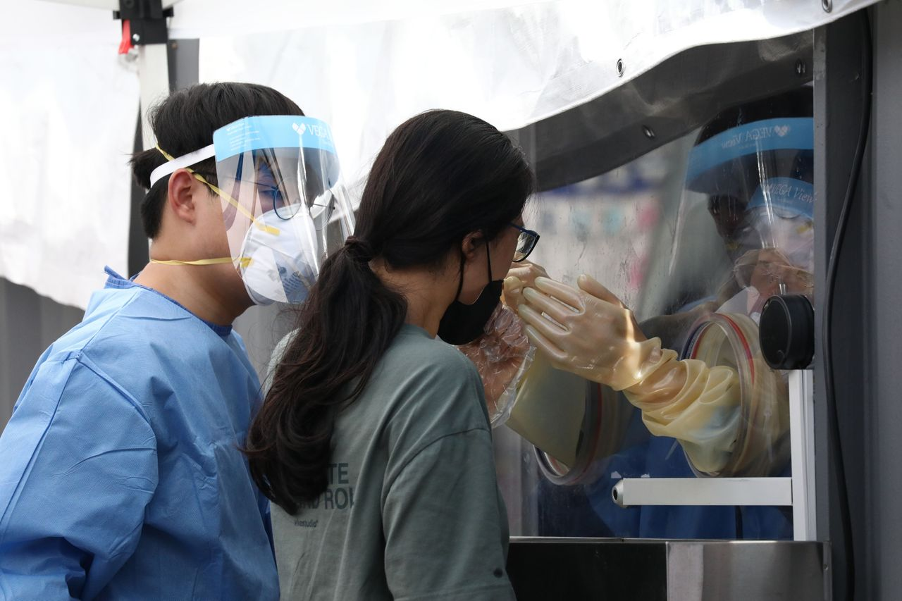 A medical worker takes samples from a woman during the COVID-19 testing at a temporary test facility on Aug. 26 in Seoul, South Korea. Anyone who has symptoms in <strong>Korea,</strong> or who may have contacted a person confirmed to have the virus, regardless of symptoms, can get tested.