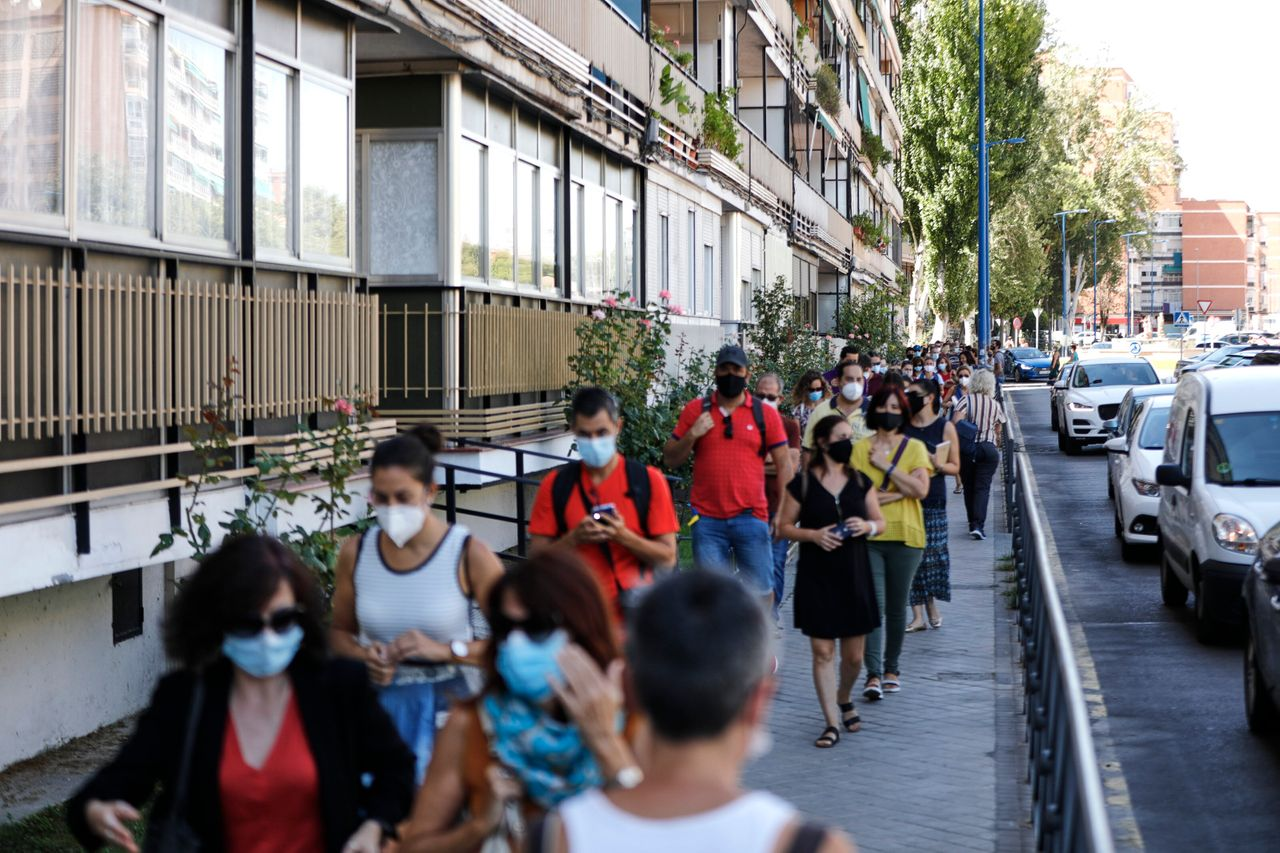 Teachers and administrative staff wait near the María Zambrano Secondary School for coronavirus tests on Sept. 3 in Madrid. There have been reports of people having to wait for days to more than a week for results.