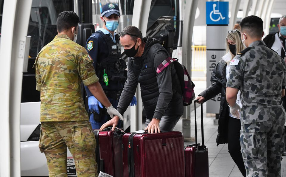 Passengers hand over their luggage to enter a hotel quarantine at Sydney International Airport on Aug....