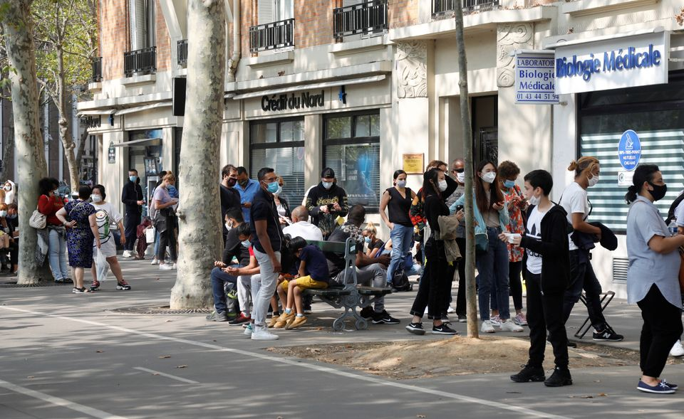 People wait in line at a testing site for COVID-19 in Paris on Sept. 11.Lab workers in France say...