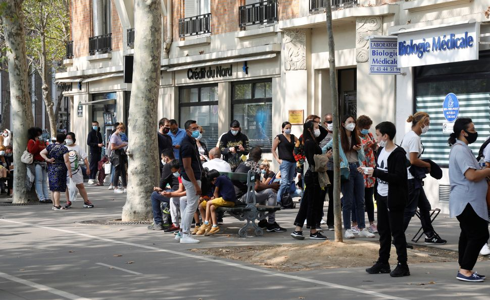 People wait in line at a testing site for COVID-19 in Paris on Sept. 11. Lab workers in France say they have become over