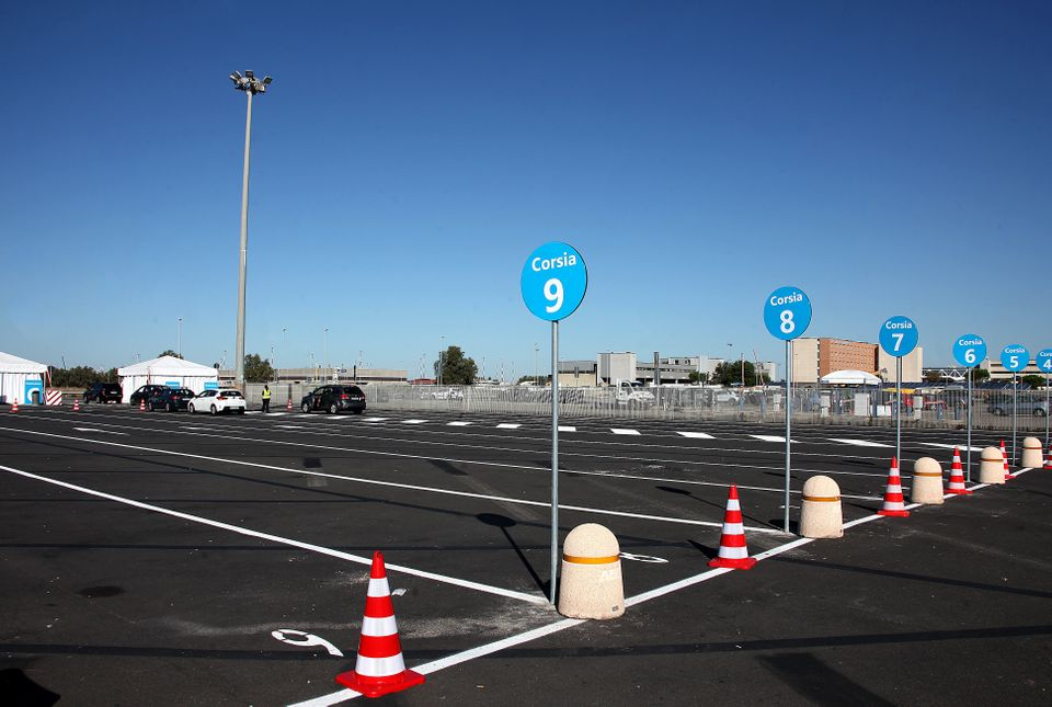 People in cars line up to be tested for COVID-19 at a drive-through testing center at a parking area...