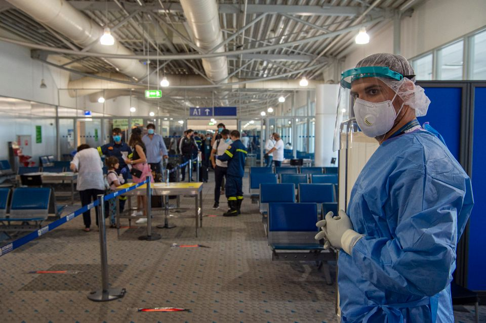 Medical staff wait to test passengers who arrive into Athens, whereauthorities perform random