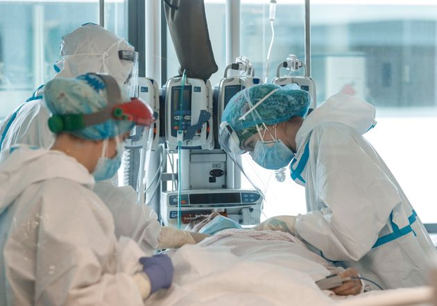 Paciente con covid en una UCI es atendido por personal sanitario,