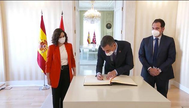 Pedro Sánchez firma ante la mirada de Ayuso y