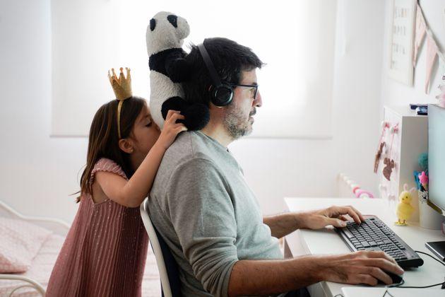 Una hija juega con oso de peluche mientras su padre trabaja desde