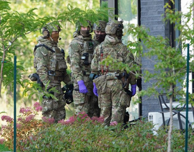 RCMP officers prepare to enter an apartment complex Monday in St-Hubert, Que., in connection with the...