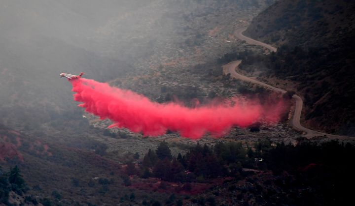 An aircraft leaves a trail of fire retardant dropped to fight the Bobcat Fire in the Angeles National Forest.