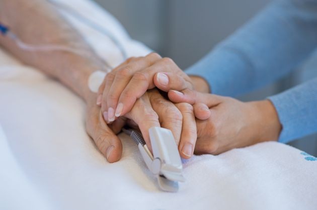 Daughter holding the hand of an elderly father. Closeup of woman holding senior man hand in hospital....