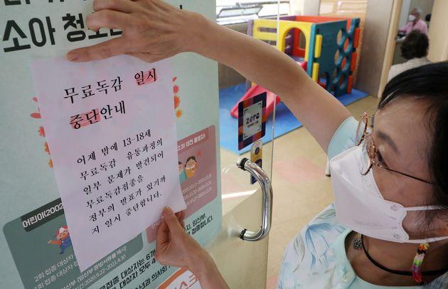 22일 오전 서울 송파구의 한 소아병원에서 간호사가 무료독감 일시중단 안내문을 붙이고