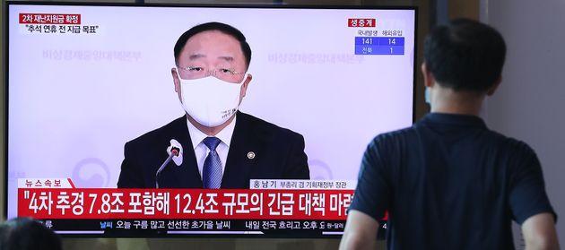 10일 오후 서울 중구 서울역에서 한 시민이 2차 긴급재난지원금 지급 관련 뉴스를 지켜보고