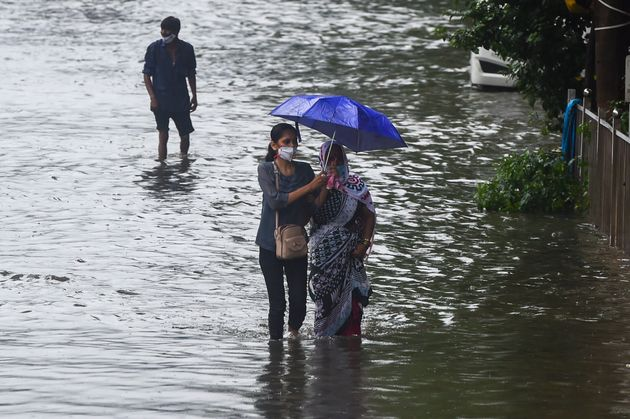 People wade through a flooded street in Mumbai on September 23,
