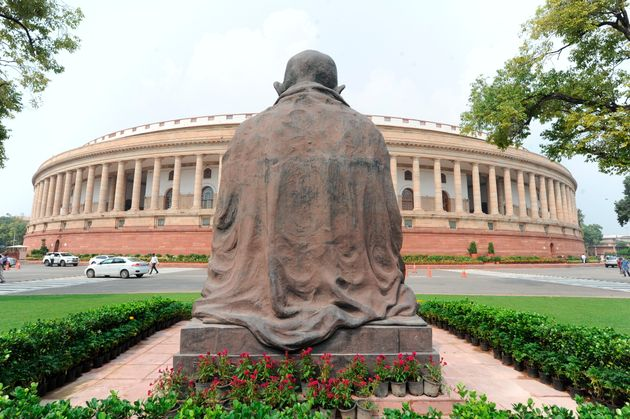 A Mahatma Gandhi statue overlooks the Parliament building as law makers arrive in New Delhi, Sept.14,