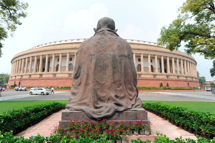 A Mahatma Gandhi statue overlooks the Parliament building as law makers arrive in New Delhi, Sept.14, 2020.