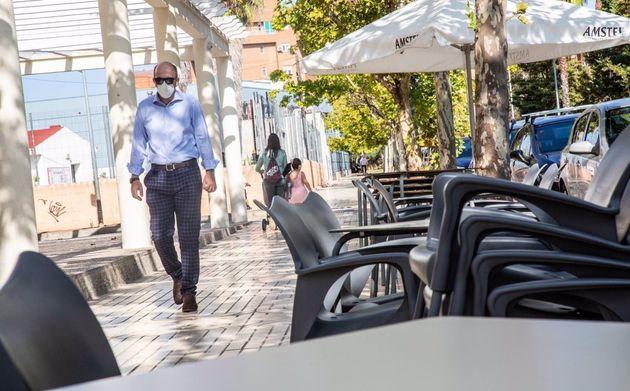 Un hombre camina junto a la terraza de un