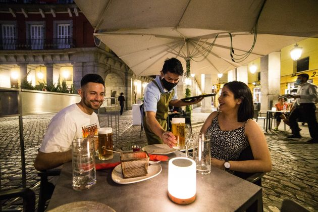 Un camarero sirve a unos clientes en la plaza Mayor de