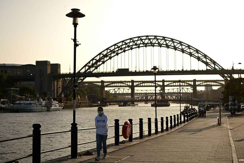 A woman wearing a protective face mask walks along the quayside, on the banks of the River Tyne, backdropped by the Tyne Bridge in Newcastle.